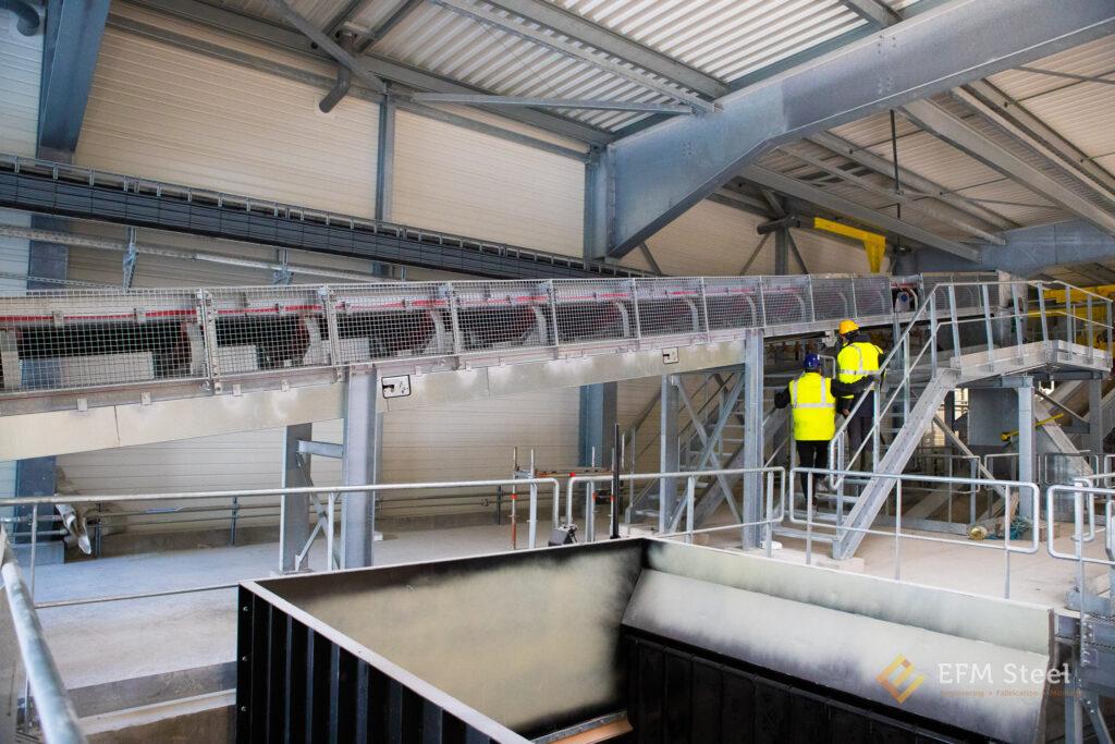 Sécurisation des parties mobiles et des points rentrants sur le transporteur T2 au moyen de grilles verticales sur la partie supérieure et au moyen de bacs en tôles pliées sur la partie inférieure.