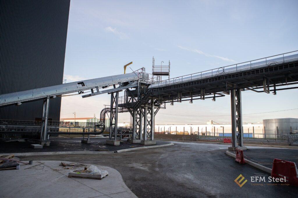 Tour d'angle pour transfert des mâchefers entre le transport T1 de collecte sous chaudière et le transporteur T2 de liaison qui a pour fonction d'acheminer les mâchefers vers la zone de préparation et de stockage.